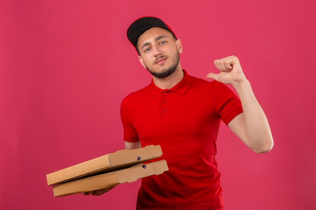 Young delivery man wearing red polo shirt and cap standing with stack of pizza boxes looking at camera smiling cheerfully proud and self-satisfied over isolated blue background