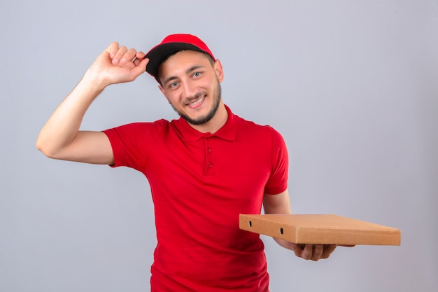 Young delivery man wearing red polo shirt and cap standing with stack of pizza boxes making greeting gesture touching cap smiling friendly over isolated white background