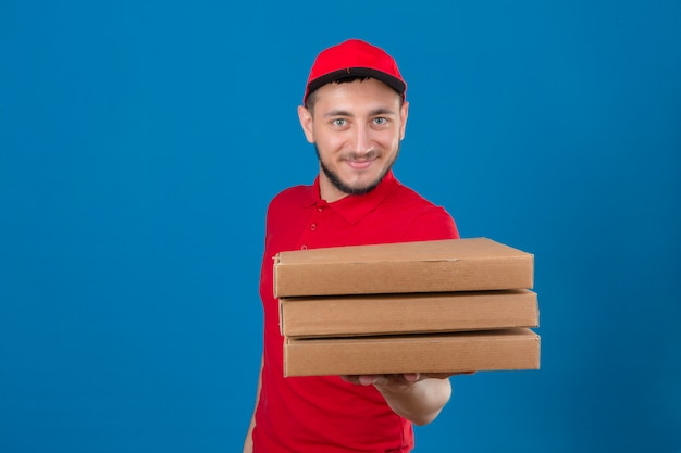 Giovane uomo di consegna che indossa la maglietta polo rossa e cappuccio stendendo una pila di scatole per pizza con il sorriso sul viso isolato su sfondo blu