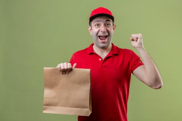 격리 된 녹색 배경 위에 행복한 얼굴로 승리를 축하하는 주먹을 올리는 종이 패키지를 들고 빨간색 유니폼을 입고 젊은 배달 남자