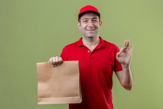 고립 된 녹색 배경 위에 확인 서명 하 고 친절 하 고 웃 고 종이 패키지를 들고 빨간 유니폼을 입고 젊은 배달 남자