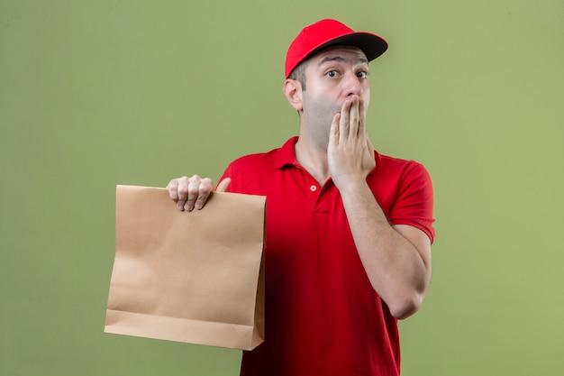 종이를 들고 빨간색 유니폼을 입고 젊은 배달 남자는 고립 된 녹색 배경 위에 손으로 입을 덮고 충격