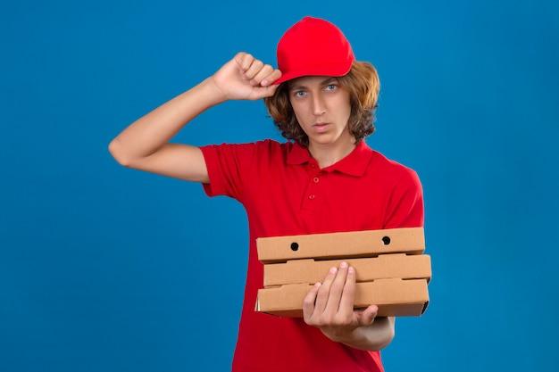 分離の青い背景に深刻な顔で彼の帽子に触れる挨拶ジェスチャーを作るピザの箱を保持している赤い制服を着ている若い配達人