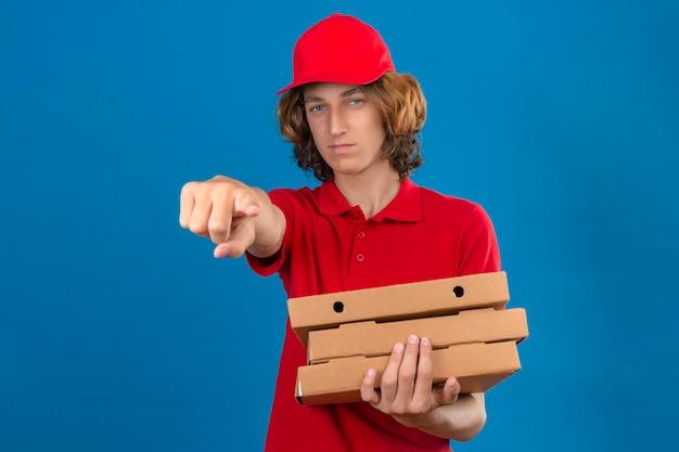 Молодой курьер в красной форме держит коробки для пиццы, недовольно и разочарованно указывая в камеру на изолированном синем фоне