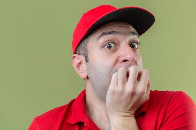 孤立した緑の背景の上に爪をかむ口に手でストレスと緊張の赤い制服を着ている若い配達人