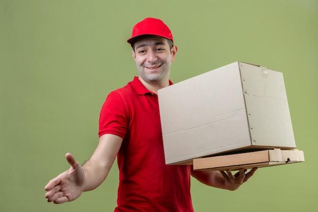 Молодой курьер в красной форме делает приветственный жест, предлагая руку, держа картонные коробки и улыбаясь на изолированном зеленом фоне