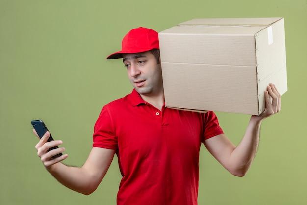 孤立した緑の背景の上の顔に悲しそうな表情で彼のスマートフォンの画面を見て彼の肩に段ボール箱で赤い制服立って身に着けている若い配達人