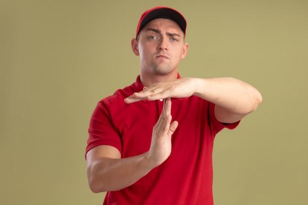 オリーブグリーンの壁に分離されたタイムアウトジェスチャーを示す制服とキャップを身に着けている若い配達人