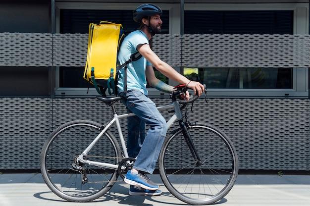 Молодой доставщик с желтым рюкзаком на вынос концепции