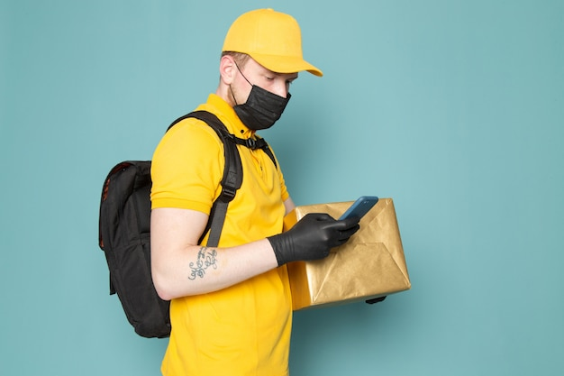 Young delivery man in yellow polo yellow cap white jeans backpack and black sterile mask holding a box on blue