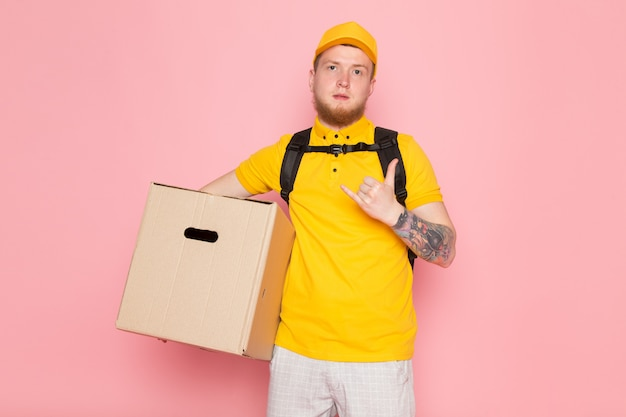 Young delivery man in yellow polo yellow cap white jeans holding a box on pink