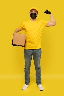 Young delivery man in yellow tshirt, mask, gloves with box isolated