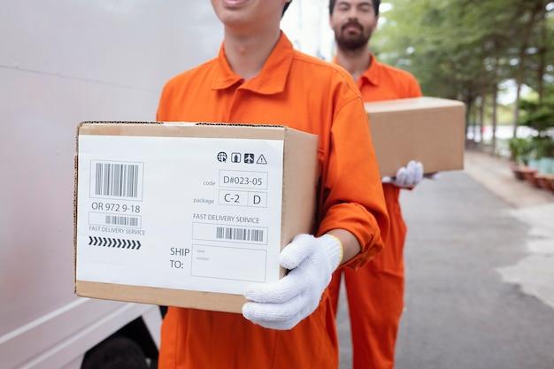 Giovani uomini di consegna che spostano scatole fuori dall'automobile
