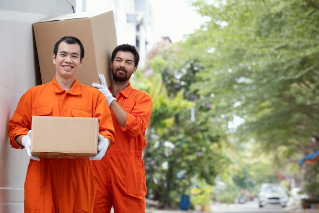 Young delivery men moving parcel boxes