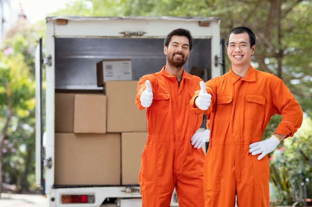 Young delivery men showing ok sign near delivery car