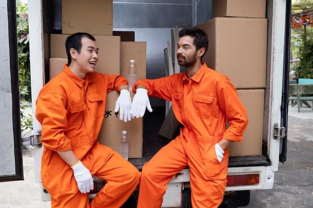 Giovani uomini di consegna che prendono una pausa vicino all'automobile di consegna