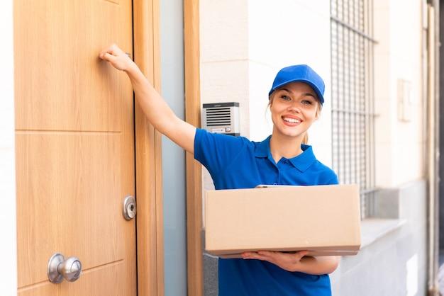 Молодая женщина доставки на открытом воздухе держит коробки и стучит в дверь