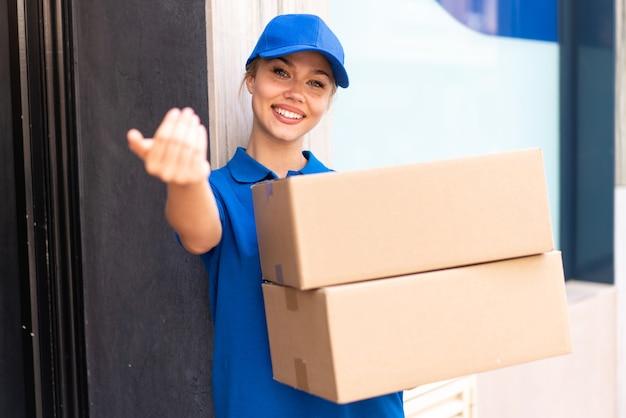 幸せな表情でボックスを保持し、来るジェスチャーをしている屋外で若い出産女性