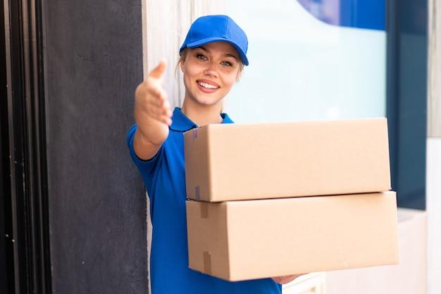 取引をしている幸せな表情でボックスを保持している屋外で若い配達の女性