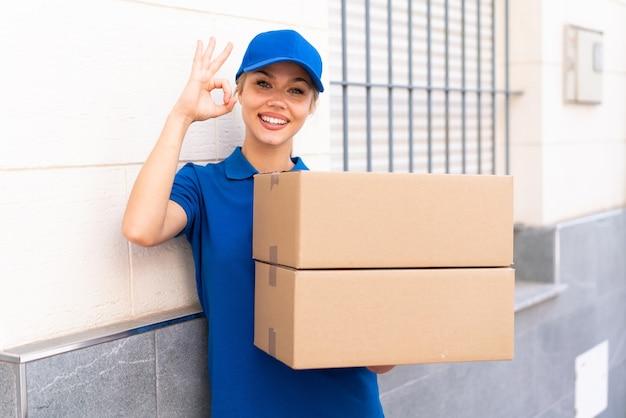 Молодая женщина доставки на открытом воздухе, держащая коробки с счастливым выражением лица
