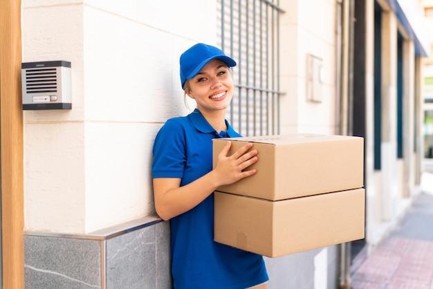 幸せな表情で箱を保持している屋外で若い配達の女性