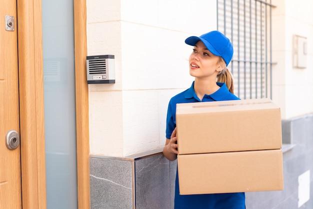 箱を保持している屋外で若い配達の女性