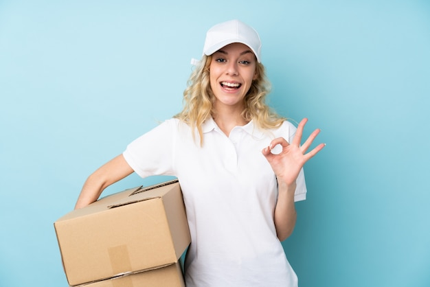 Young delivery woman on blue showing an ok sign with fingers