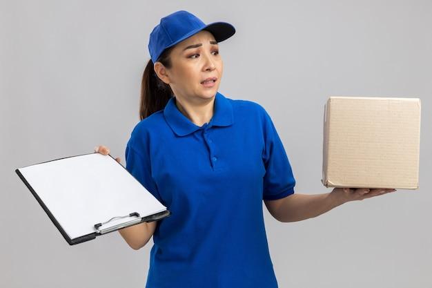 Giovane donna delle consegne in uniforme blu e cappuccio con scatola di cartone e appunti guardando da parte confuso in piedi sul muro bianco