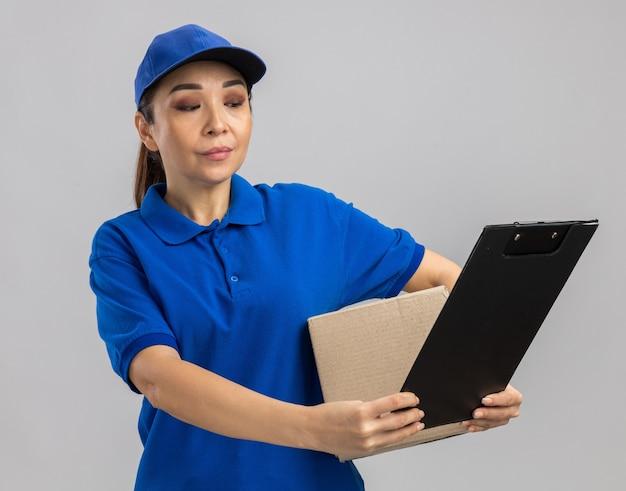 Giovane donna delle consegne in uniforme blu e berretto con scatola di cartone e appunti che sembra sicura di sé in piedi sul muro bianco white