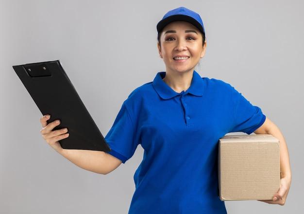 Giovane donna delle consegne in uniforme blu e berretto che tiene in mano una scatola di cartone e appunti sorridenti sicuri in piedi sul muro bianco