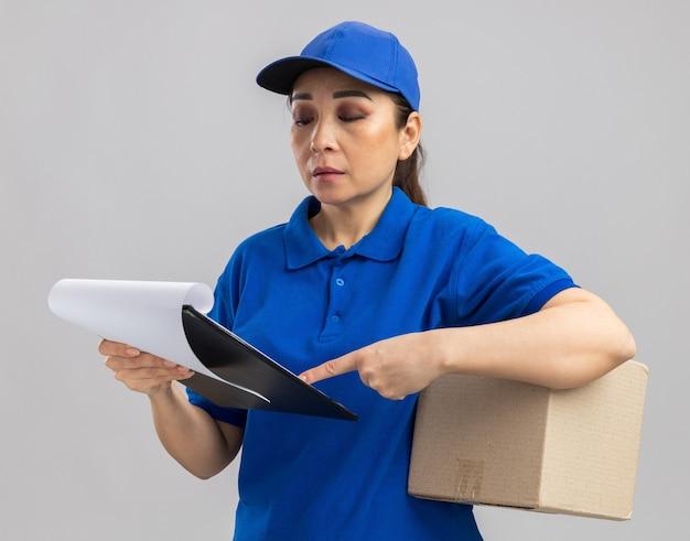 Giovane donna delle consegne in uniforme blu e berretto con scatola di cartone e appunti con pagine bianche che lo guardano con una faccia seria in piedi su un muro bianco