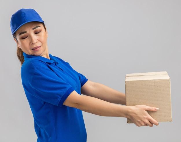 Giovane donna delle consegne in uniforme blu e cappuccio che tiene una scatola di cartone che guarda da parte con un'espressione disgustata in piedi sul muro bianco white