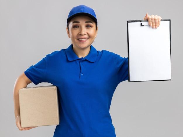Giovane donna delle consegne in uniforme blu e cappuccio che tiene una scatola di cartone che mostra appunti con pagine bianche sorridenti fiduciosi in piedi sul muro bianco