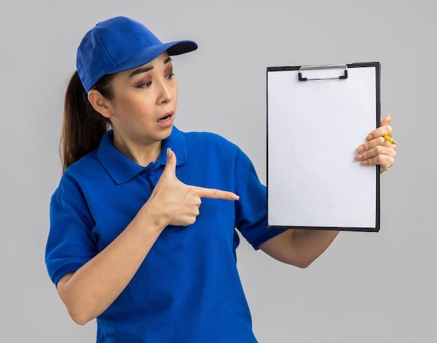 Giovane donna delle consegne in uniforme blu e berretto che tiene appunti con pagine bianche che puntano con il dito indice sorpreso in piedi sul muro bianco