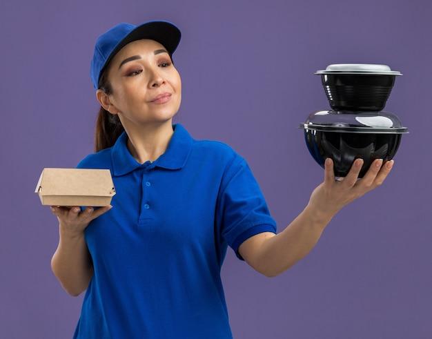 Giovane donna delle consegne in uniforme blu e berretto che tiene in mano pacchi di cibo guardandoli con un sorriso sul viso in piedi sul muro viola purple
