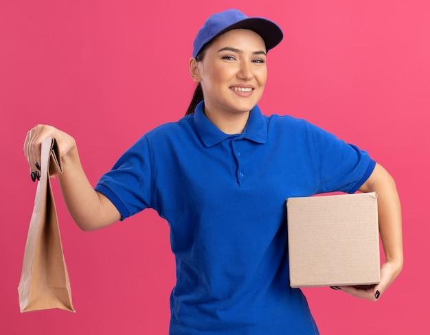 Giovane donna di consegna in uniforme blu e cappuccio che tiene il pacchetto di carta e la scatola di cartone guardando davanti sorridente fiducioso in piedi sopra la parete rosa