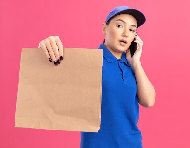 Giovane donna di consegna in uniforme blu e cappuccio che tiene il pacchetto di carta guardandolo con faccia seria mentre parla al telefono cellulare in piedi sopra il muro rosa