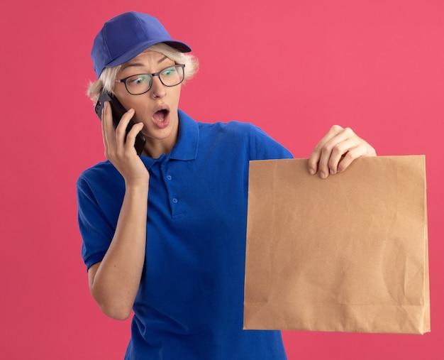 Giovane donna di consegna in uniforme blu e cappuccio che tiene il pacchetto di carta che sembra sorpreso e stupito mentre parla al telefono cellulare sopra il muro rosa