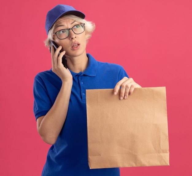 Giovane donna delle consegne in uniforme blu e cappuccio che tiene il pacchetto di carta parlando al telefono cellulare che osserva da parte perplessa sul muro rosa