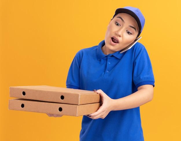 Giovane donna delle consegne in uniforme blu e cappuccio che tiene le scatole per pizza essendo sorpresa a parlare al telefono cellulare in piedi sopra la parete arancione