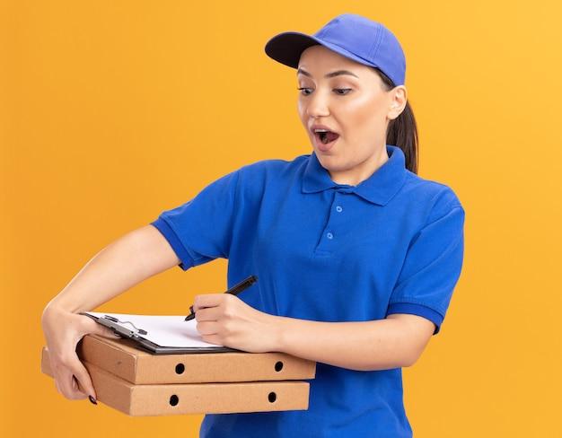 Giovane donna di consegna in uniforme blu e cappuccio che tiene scatole di pizza e appunti con scrittura a matita in piedi felice ed eccitato sopra la parete arancione