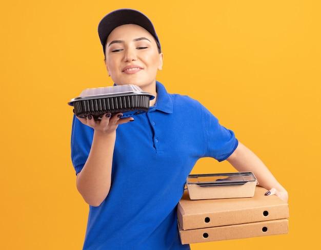Giovane donna delle consegne in uniforme blu e cappuccio che tiene scatole per pizza e confezioni di cibo inalando aroma gradevole in piedi sopra la parete arancione