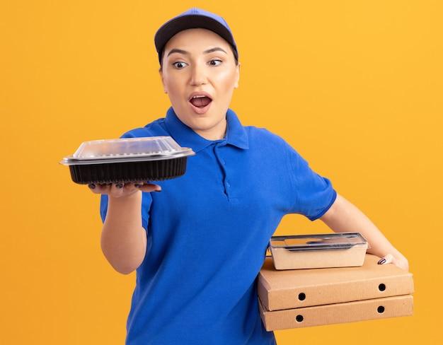 Giovane donna di consegna in uniforme blu e cappuccio che tiene scatole per pizza e confezioni di cibo guardando scatole stupite e sorprese in piedi sopra la parete arancione