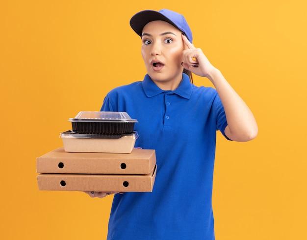 Giovane donna delle consegne in uniforme blu e cappuccio che tiene scatole per pizza e confezioni di cibo guardando davanti che punta con il dito indice al suo tempio guardando confuso in piedi sopra la parete arancione