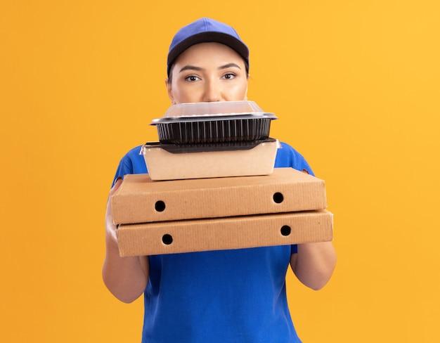 Giovane donna delle consegne in uniforme blu e cappuccio che tiene scatole per pizza e confezioni di cibo guardando la parte anteriore con la faccia seria in piedi sopra la parete arancione