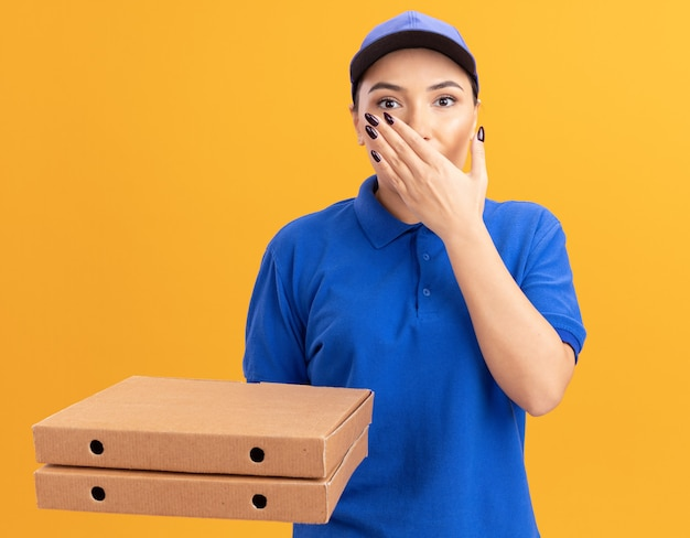 Young delivery woman in blue uniform and cap holding pizza boxes looking at front being shocked covering mouth with hand standing over orange wall