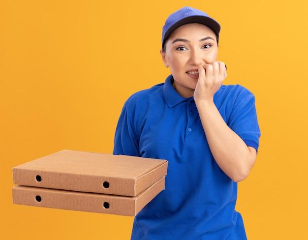 Giovane donna delle consegne in uniforme blu e cappuccio che tiene le scatole per pizza guardando le unghie mordaci stressate e nervose frontali in piedi sopra la parete arancione