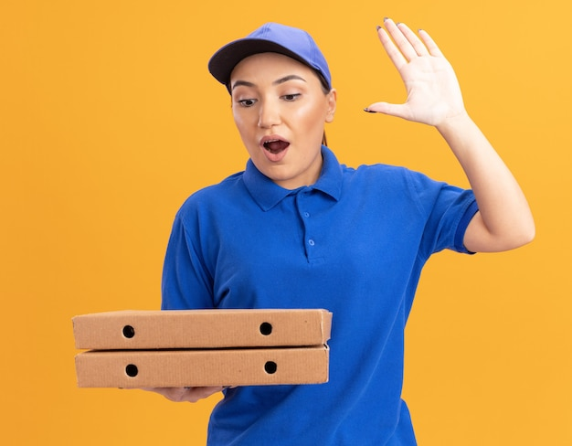 Giovane donna di consegna in uniforme blu e cappuccio che tiene le scatole per pizza guardandole stupita e sorpresa alzando la mano in piedi sopra il muro arancione
