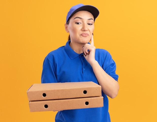 Giovane donna delle consegne in uniforme blu e cappuccio che tiene le scatole per pizza guardandole con espressione pensierosa sul viso in piedi sopra la parete arancione