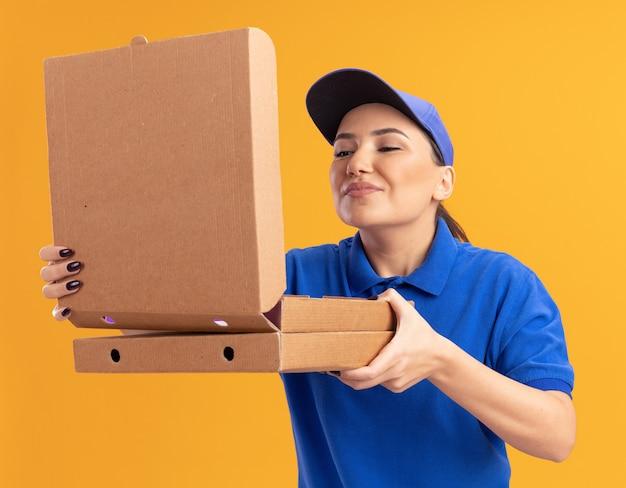 Giovane donna delle consegne in uniforme blu e cappuccio che tiene la scatola di apertura delle scatole della pizza inalando un aroma piacevole in piedi sopra la parete arancione